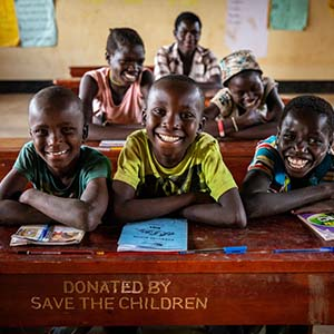 A group of three smiling school boys sit at a desk donated by Save the Children within the Kyangwali Refugee Settlement in Uganda.]