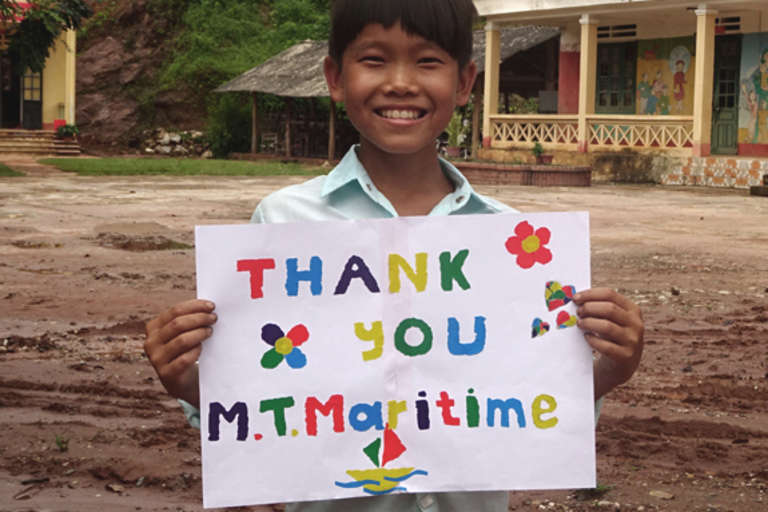 Bang is a 9-year-old from Vietnam who is enrolled in Save the Children's sponsorship program holds up a sign thanking MT Maritime for their support. Photo credit: Save the Children 2017.