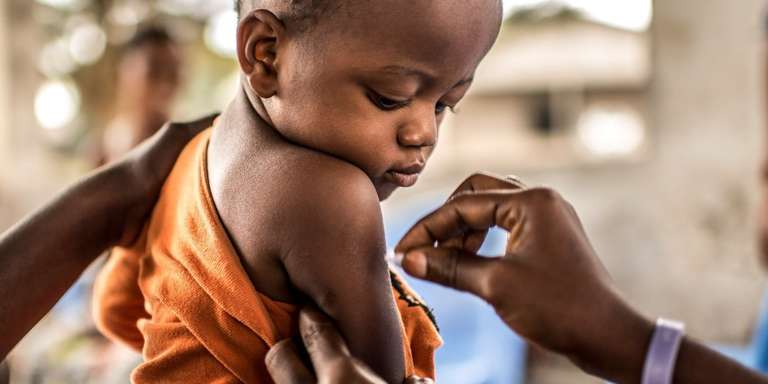 A one-year-old child prepares to receive his Yellow Fever vaccination in the Binza Ozone district of Kinshasa, Democratic Republic of Congo. Photo Credit: Tommy Trenchard, August 2016