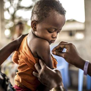 A one-year-old child prepares to receive his Yellow Fever vaccination in the Democratic Republic of Congo. Photo Credit: Tommy Trenchard, August 2016