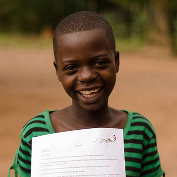 A child smiles because they have been sponsored