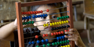 A young boy plays with an abacus.