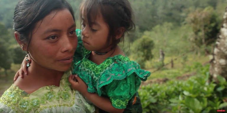 A mother from Guatemala lifts up and holds her young daughter in a lush, green garden. Photo credit: Save the Children, 2012.