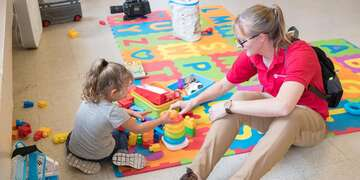 Director of US emergencies Sarah Thompson plays with 4 year old Teresa* at a New Mexico Asylum Shelter and Save the Children Child Friendly Space.