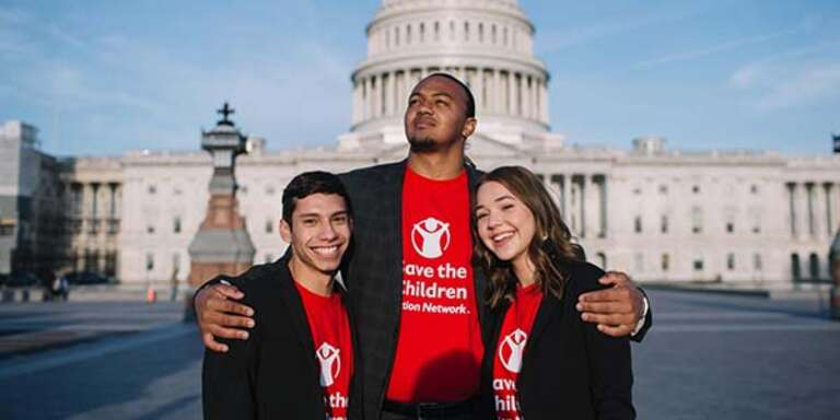 A group of three Student Ambassadors wearing red Save the Children Action Network shirts stand together in front of Capitol Hill during the 2019 Advocacy Summit.