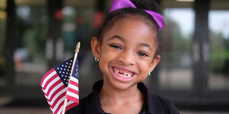 A young girl smiles while holding a small American flag on a stick in her hand.