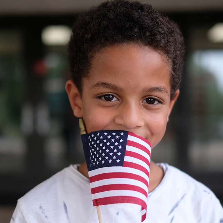A boy stands holding an American Flag