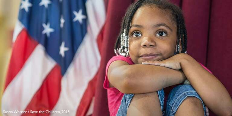 A young girl sits with her knees up to her chest. An American flag is in the background.