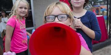 A girl holds a megaphone up to her face.