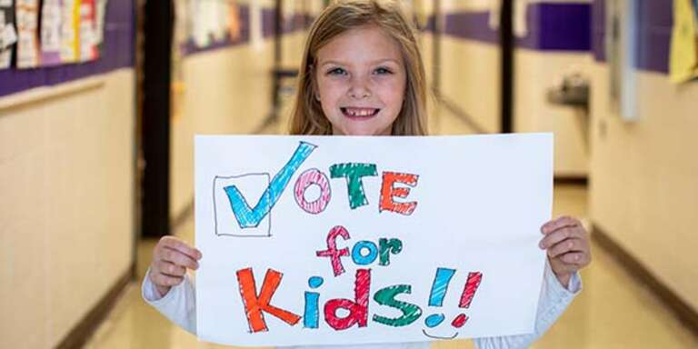7-year-old Maddie holds a hand drawn sign saying 'Vote for Kids' in the hallway of her elementary school.