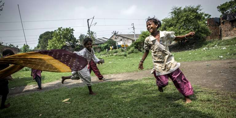 Children of the Madhu Basti play games outdoors using colorful fabric as a toy. Photo credit: CJ Clarke / Save the Children, May 2015.