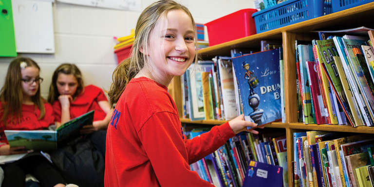 A smiling 10-year-old girl picks a book off a shelf at an in-school literacy program, in Whitley County, Kentucky. Photo credit: Victoria Zegler/Save the Children, December 2017.