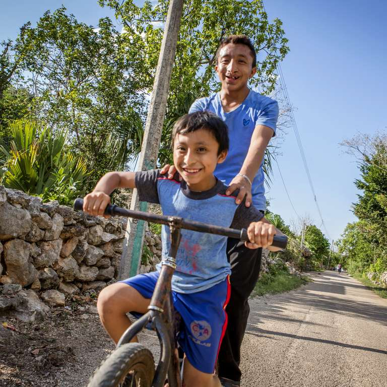 Rudi, aged 9, and brother Orlando, 18, ride a bicycle in the Mayan village where they live in Yucatan state, Mexico. Photo credit: Jonathan Hyams / Save the Children 2016.