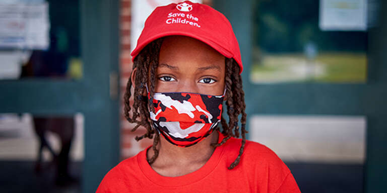 A boy wears a red Save the Children hat and a cloth face mask while standing outside.