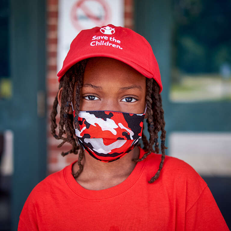 A young student wearing a face mask and red hat enjoys a break from Save the Children's virtual summer camp program.