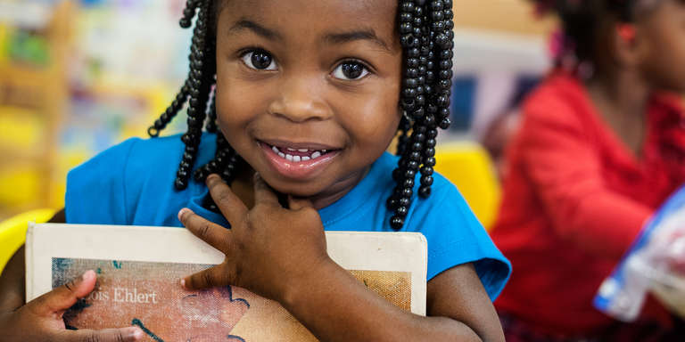A smiling pre-school student clutches a book to her chest at the Early Steps for School Success program (ESSS) in Barnwell, South Carolina: Photo credit: Susan Warner/Save the Children, October 2014.