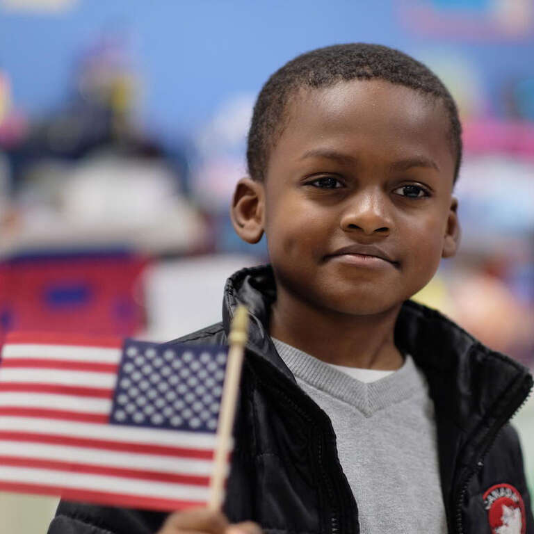 A child smiles and holds an American flag.