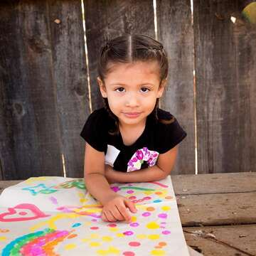 A 3-year old girl named Analia sits at a picnic table outside and displays a colorful painting in front of her. The girl and her mom participated in several learning-based activities taught to them during a home visit as part of Save the Children's signature Early Steps to School Success program. Photo credit: Save the Children, Nov 2017.