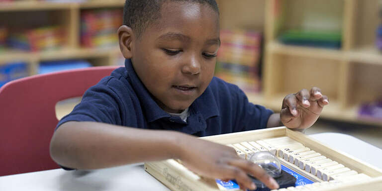 A young boy in a blue shirt plays a numeracy game.