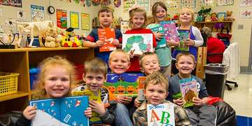 A group of first grade students hold up favorite books in their classroom in Kentucky.