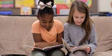 Taylor, age 7, left, and classmate Tara, age 8, read together during Save the Children's Guided Independent Reading Practice at their school in Tennessee.