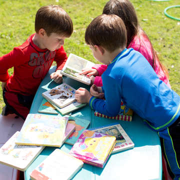 Easton, Kellen and Ada share a book on the playground at Save the Children's Head Start center in Arkansas, on April 27, 2017. Photo credit: Eli Murray / Save the Children 2017.
