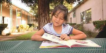 A girl reads a picture book while seated outside at a picnic table.