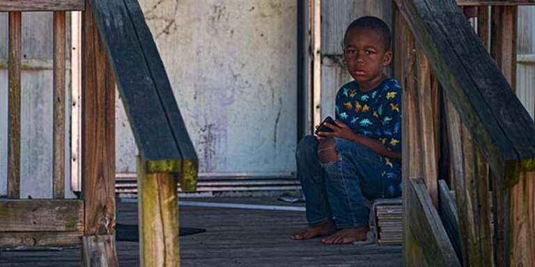 A young boy sits outside on the wooden porch of his home in South Carolina.