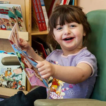 Two-year-old Michelle enjoys the reading corner at the Alamosa Family Medical Center. The reading corner is a new community initiative with local business, housing communities and doctors offices to foster everyday reading with children. Photo credit: Susan Warner / Save the Children 2016.