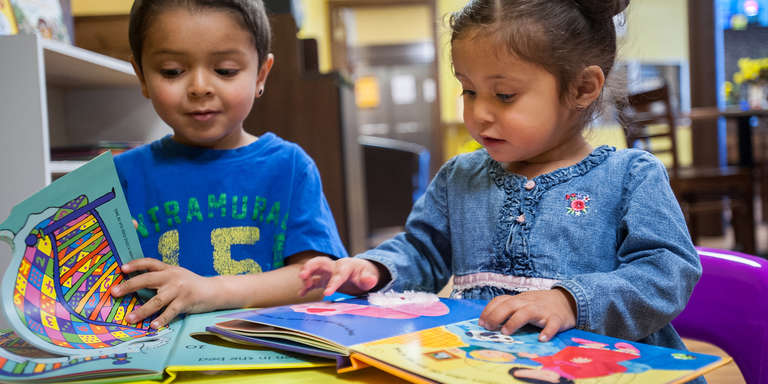 Two young children sit at a table together and look at colorful picture books. Save the Children's early learning programs promote reading from a young age. Photo credit: Susan Warner / Save the Children, April 2016.