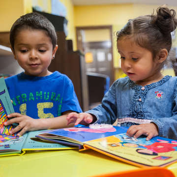 Two young children sit at a table together and look at colorful picture books. Save the Children's early learning programs promote reading from a young age. Photo credit: Susan Warner / Save the Children 2016.