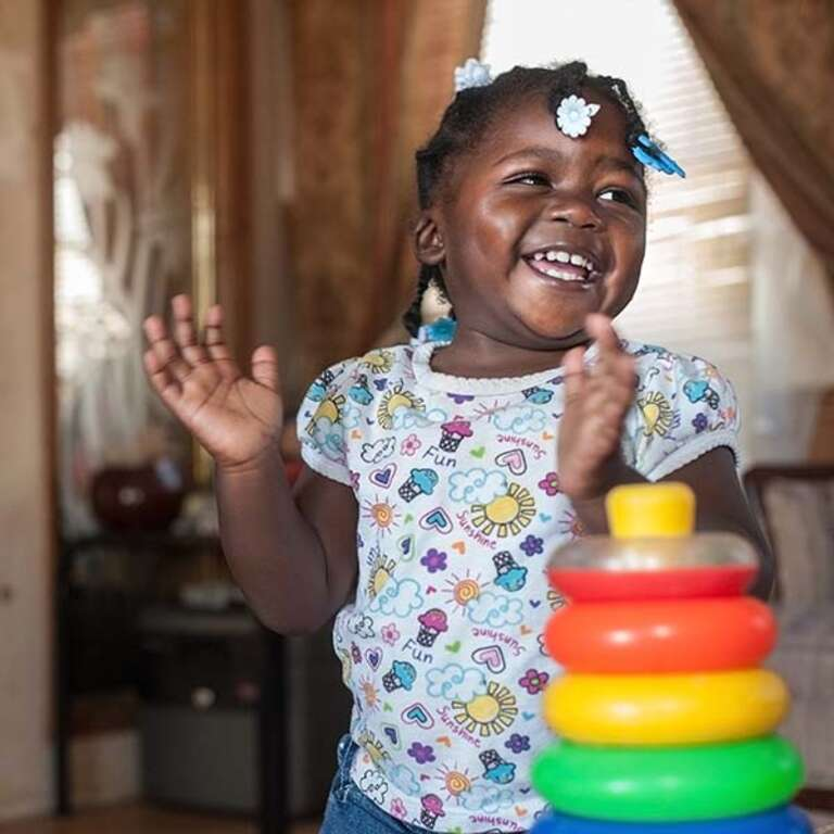 A young girl claps her hands in delight while standing near a set of colorful blocks in her home in Mississippi.