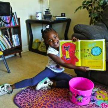 A 4 year old holds up her book