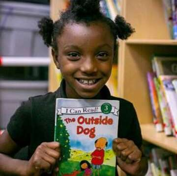 "A student holds the book ""The Dog Outside""."