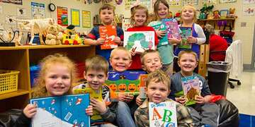 A group of first grade students hold up favorite books in their classroom in Kentucky. They are part of Save the Children's in school emergent reader program which provides training, tools and support schools need to accelerate reading growth for struggling readers. March 2018