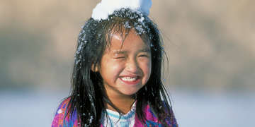 A girl plays outside in the snow