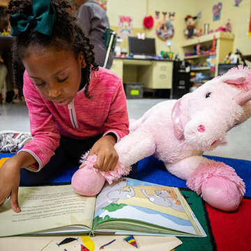 8-year-old Aiyana reads a book quietly to her reading buddy Bianca in the Save the Children classroom in Mississippi.