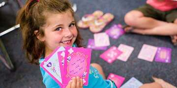 A girl holds a stack of pink playing cards as she enjoys a game with friends at school.