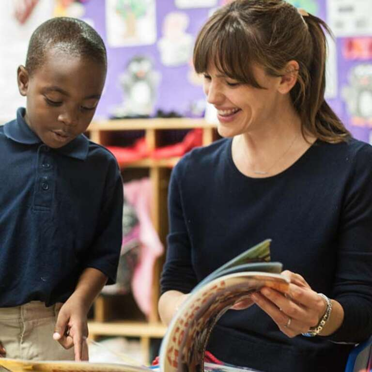 Save the Children Trustee Jennifer Garner enjoys reading a book with a young student.]