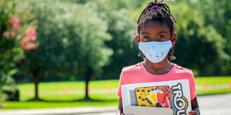A young girl wears a cloth face mask white standing outside in South Carolina.