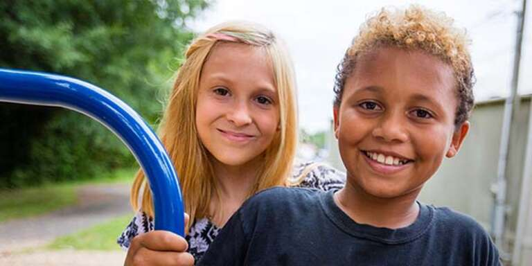 Two young children stand together near a school playground in Tennessee and smile widely