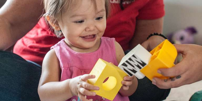 A young girl plays with yellow blocks.