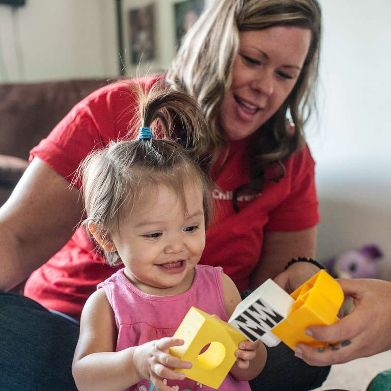A Save the Children employee plays blocks with a smiling, toddler-aged girl during an Early Steps to School Success home visit in Washington state. Photo credit: Susan Warner / Save the Children, November 2015.