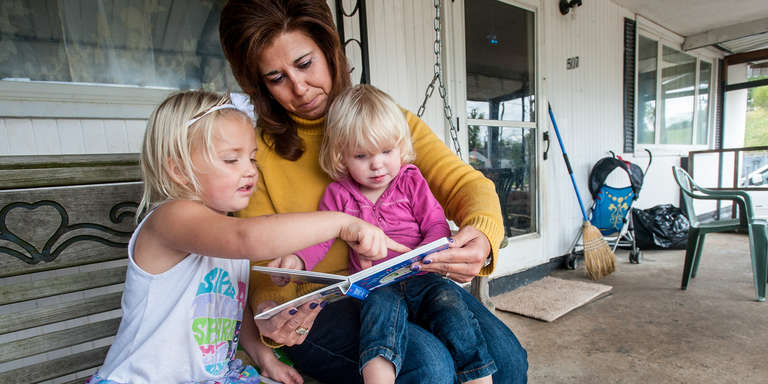 Two children read with an adult outside