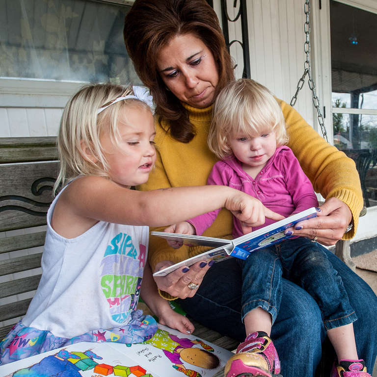 A woman and two children read a book together on their porch.