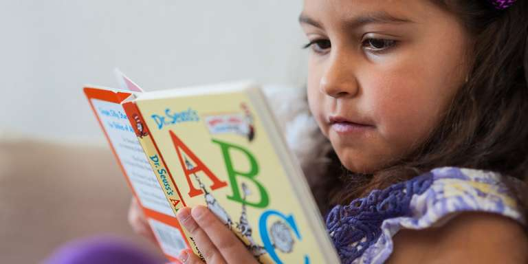 A close up shot of a young girl read a book with ABC on the cover.
