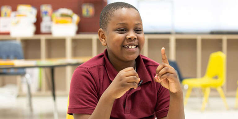 A young boy counts with his hands by holding up one finger.