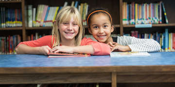 Two third-grade girls, Madison and Justine, smile in the school library at the Save the Children-sponsored afterschool literacy program. The program is held in their elementary school in West Virginia. Photo credit: Susan Warner/Save the Children, February 2015.