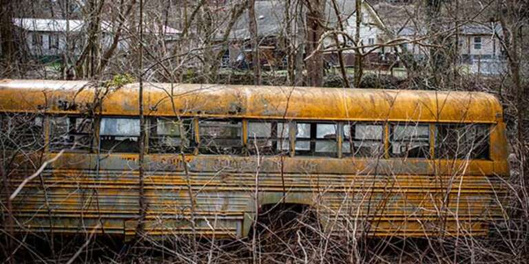 An abandon yellow school bus with broken windows rust in a field in County, West Virginia.