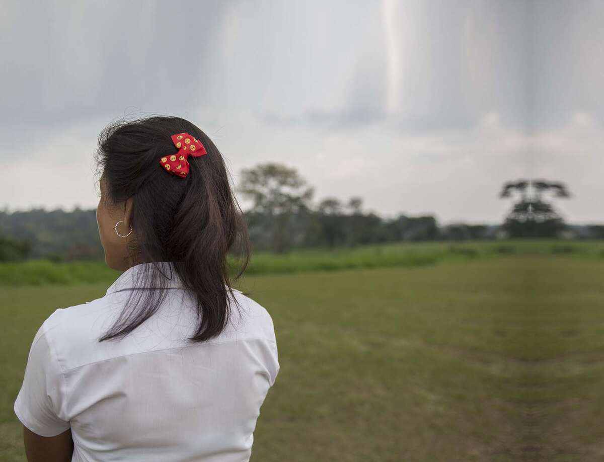 A 14-year old girl stands with her arms cross while looking out over a grassy field in El Salvador.